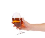 Glass of beer with foam in hand. Stock Photos