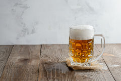 Glass of beer with foam on a wooden background royalty free stock photo