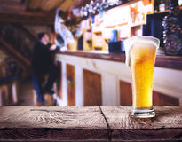Glass of beer with foam on wooden table Stock Image