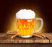 Glass of beer. Foamy beer on a wooden table and spike Royalty Free Stock Photography