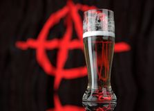 A glass of beer in front a anarchist flag. 3D illustration rendering. Stock Photos