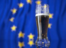 a glass of beer in front a European Union, flag. 3D illustration rendering. Royalty Free Stock Photos