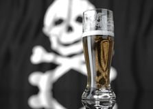 A glass of beer in front a pirate flag. 3D illustration rendering. Stock Photos
