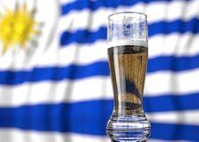 A glass of beer in front a Uruguayan flag. 3D illustration rendering. Royalty Free Stock Photo
