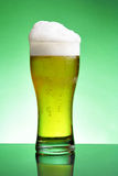 Glass of beer with froth Stock Photography