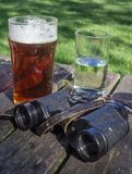 Glass of Beer, Fruit Drink and Binoculars Royalty Free Stock Photo