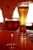 Glass of beer and a glass of red wine. Glass of cold beer and a glass of red wine Royalty Free Stock Photography