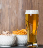 Glass of beer, golden chips and  pistachios in bowl Stock Photography