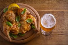 Glass of beer and grilled chicken. Well-baked and juicy chicken is good food to glass of ale. Beer and meat. Overhead, horizontal royalty free stock images
