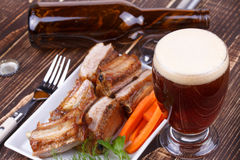 Glass of beer, grilled pork ribs and fresh carrot Stock Image