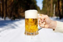Glass of beer in hand . stock image