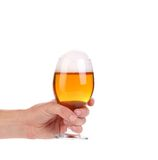 Glass of beer in hand. Royalty Free Stock Image