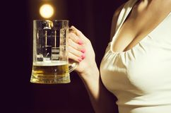 Glass of beer in hand of sommelier woman. Glass of beer in hand of sommelier women in dress near mirror with lamps, meeting and relax, bar and restaurant royalty free stock image