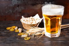 Glass with beer and a head of foam near plate with pistachios, w. Heat, scattered small pretzels and peanuts on dark desk. Food and beverages concept Stock Image