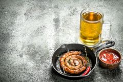 Glass of beer with hot sausage. On a rustic background Stock Image
