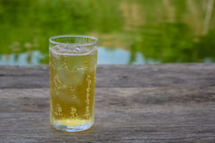 A glass of beer with ice on wooden table, drinking in hot Asian country with cool soft drink Stock Image