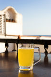 Glass of beer with lemon near the sea. Stock Image