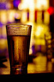 Glass. A glass of beer with luminous background on a bar Royalty Free Stock Photo