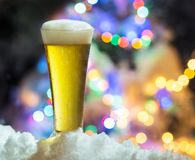 Glass of beer with magic Christmas lights at the background royalty free stock photos