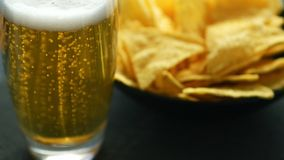 Glass of beer and nacho chips. Transparent glass of light beer with foam and bowl of crispy golden nacho chips served on table Royalty Free Stock Photography