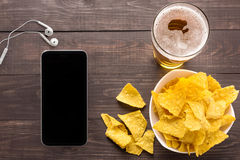 Glass of beer with nachos chips on a wooden background Stock Photography
