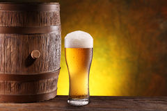 The glass of beer near woden barrel. The glass of beer near old woden barrel royalty free stock photo