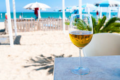 Glass of Beer Outdoors. Half empty glass of beer in shadow on sandy beach royalty free stock image