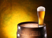 The glass of beer over woden barrel. The glass of beer over woden barrel on the golden background Stock Photography