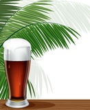 Glass of beer and palm branches. Glass of beer with foam and palm branches on a bar counter Royalty Free Stock Photography
