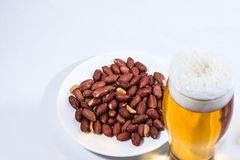 A glass of beer and peanuts in the saucer royalty free stock image