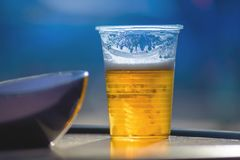 Glass of beer in a plastic cup. Blue background stock photo