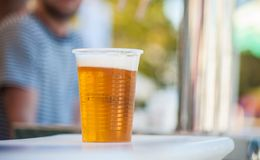 Glass of beer in a plastic cup.  stock photography
