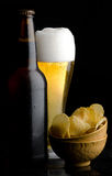 Glass of beer and potato chips. Beer bottle and glass of beer and potato chips Royalty Free Stock Photo
