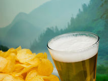 Glass of beer and potato chips Royalty Free Stock Photos