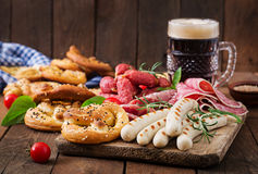Glass of beer, pretzels and various sausages Stock Image