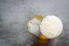 Glass of beer and a puddle of beer on the table Stock Images