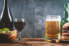 Glass of Beer and red wine. With copy space for text on chalk board background Royalty Free Stock Images