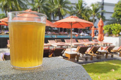 Glass of beer on resort swimming pool background. Royalty Free Stock Images