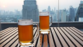 Glass of draft beer with the sunset behind. royalty free stock photo
