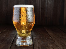 Glass beer on rustic table. Horizontal orientation. Glass cold beer with drops on dard wood table. Horizontal orientation Stock Photography