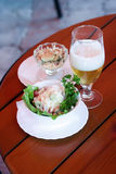 Glass of beer and salad. On a little table of summer cafe Royalty Free Stock Image