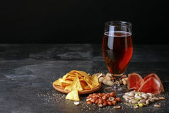 Glass of beer, salty chips, peanuts, ham on a black background. Refreshing alcoholic drinks. Tasty restaurant snacks Royalty Free Stock Photos
