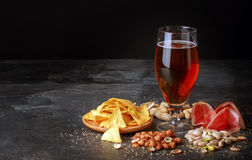 Glass of beer, salty chips, peanuts, ham on a black background. Refreshing alcoholic drinks. Tasty restaurant snacks Royalty Free Stock Images