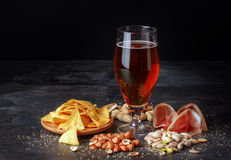 Glass of beer, salty chips, peanuts, ham on a black background. Refreshing alcoholic drinks. Tasty restaurant snacks Royalty Free Stock Photography