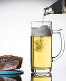 Glass of beer and salty fish. Beer flows from a bottle in a glass Stock Photo