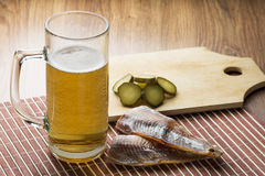 Glass of beer and salty fish. On the wood table Stock Photos