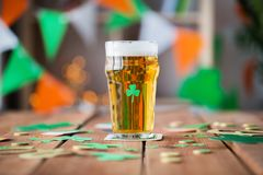 Glass of beer, shamrock and coins on wooden table Royalty Free Stock Images