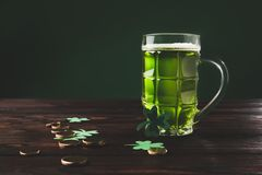 Glass of beer with shamrock and golden coins on wooden table Royalty Free Stock Photo