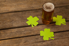 Glass of beer and shamrock for St Patricks Day. Against wooden background Stock Photo