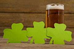 Glass of beer and shamrock for St Patricks Day. Against wooden background Royalty Free Stock Image